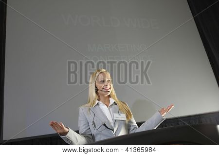Low angle view of a happy young businesswoman giving a lecture at podium