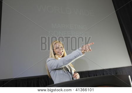 Low angle view of a happy young businesswoman pointing while giving a lecture at podium
