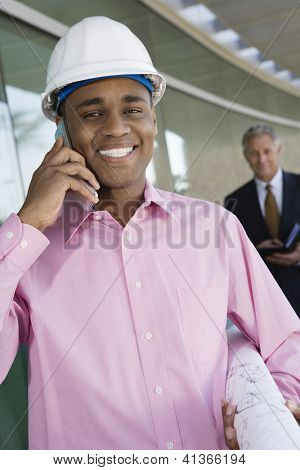 Portrait of happy architect on a call with blue print and man in the background