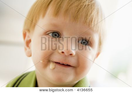 Young Boy Eating Baby Food With Mess On Face