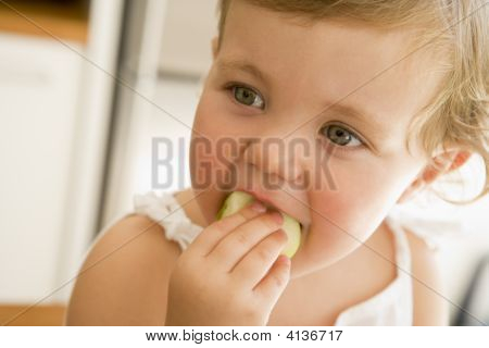 Young Girl Eating Apple Indoors