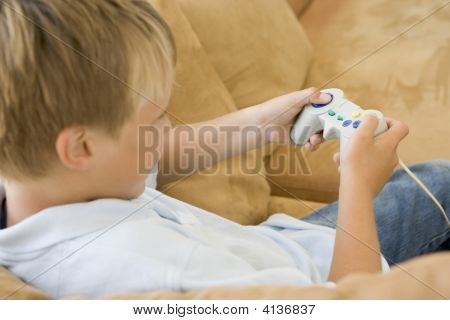 Young Boy In Living Room With Video Game Controller