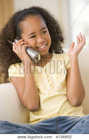 Young Girl In Living Room Using Telephone And Smiling