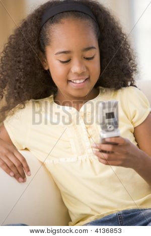 Young Girl In Living Room Using Cellular Phone And Smiling