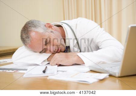 Médico com Laptop dormindo no consultório do médico