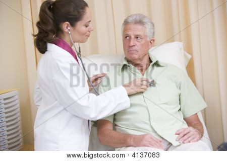 Doctor Giving Checkup With Stethoscope To Man In Exam Room