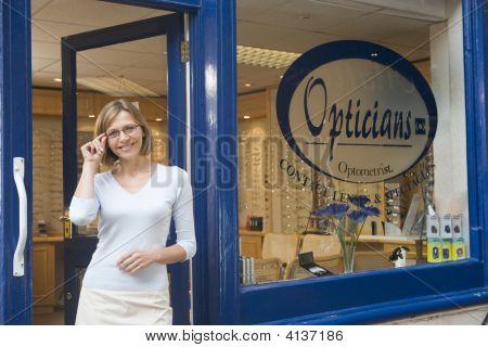 Mujer de pie en la entrada principal de optometristas sonriendo