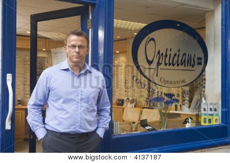 Man Standing At Front Entrance Of Optometrists