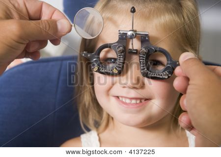 Optometrista en la sala de examen con la niña en silla sonriendo