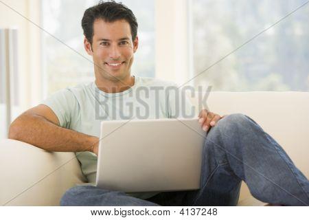 Hombre en la sala de estar usando Laptop sonriendo