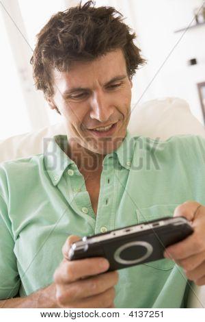 Hombre en la sala de estar jugando videojuegos mano sonriendo