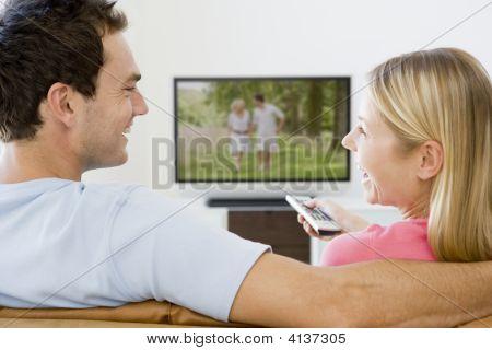 Parejas en sala de estar viendo televisión sonriendo