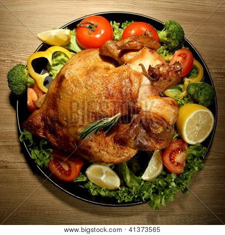 Whole roasted chicken with vegetables on plate, on wooden table
