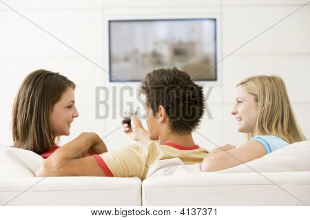 Three Friends In Living Room Watching Television Smiling