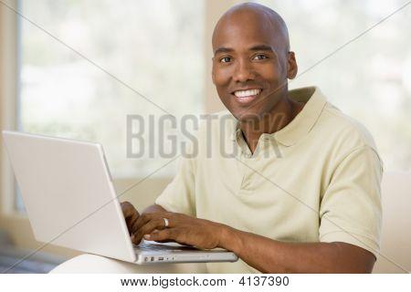 Hombre en la sala de estar usando Laptop y sonriendo