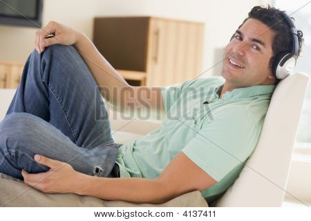 Man In Living Room Listening To Headphones Smiling