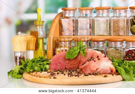 A large piece of pork marinated with herbs, spices and cooking oil on board on white table on window background