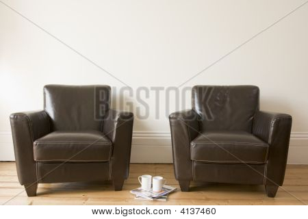 Two Chairs With Coffee Mug And Magazines Between Them