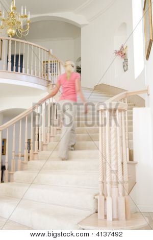 Woman Going Up Staircase In Luxurious Home
