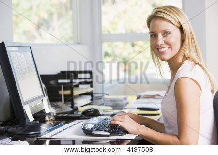 Woman in home Office with Computer lächelnd