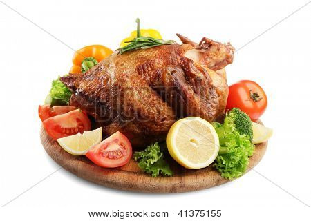 Whole roasted chicken on wooden plate with vegetables, isolated on white