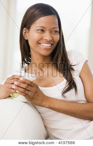 Frau im Wohnzimmer mit Kaffee zu Lächeln