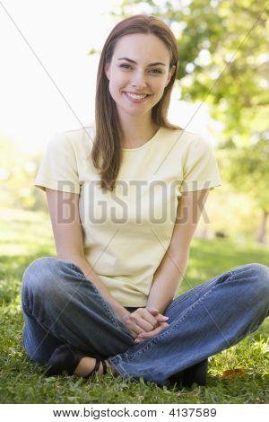 Mujer sentada sonriendo al aire libre