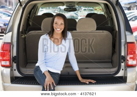 Woman Sitting In Back Of Van Smiling