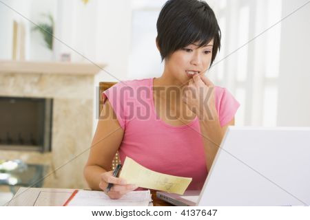 Woman In Dining Room With Laptop Thinking