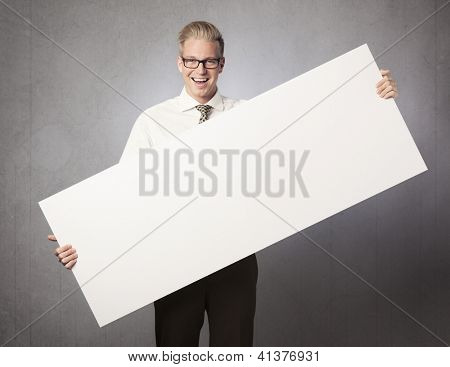 Happy businessman holding empty white panel with space for text isolated on grey background.