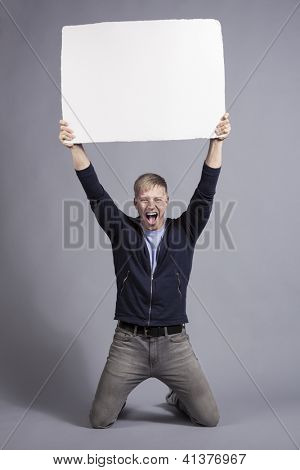Awesome news: Excited laughing man holding up white blank panel with space for text isolated on grey background.