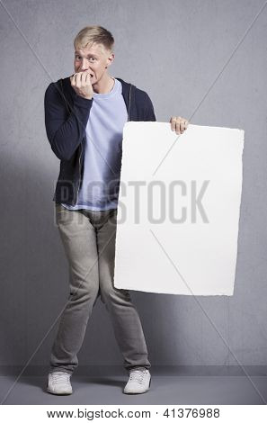 Frustrating news: Anxious man holding white blank panel with space for text isolated on grey background.