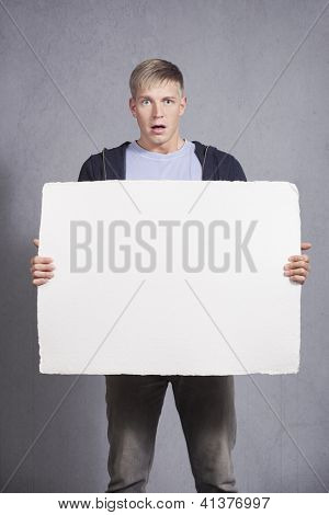 Upsetting news: Surprised man presenting white blank signboard with space for text isolated on grey background.