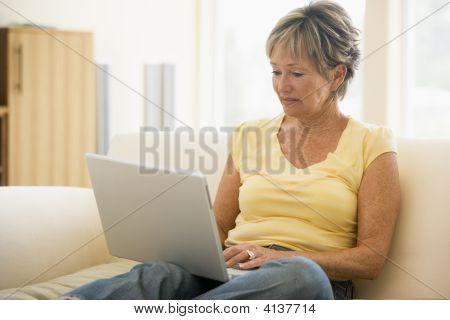 Frau in Living Room with Laptop smiling