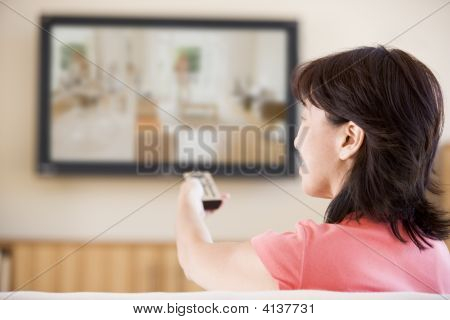 Woman Watching Television Using Remote Control