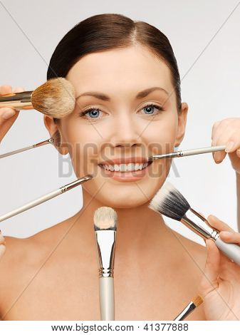 bright closeup portrait picture of beautiful woman with brushes.