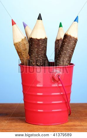 Colorful wooden pencils in pink pail on wooden table on blue background
