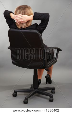 Young beautiful business woman resting on chair on grey background