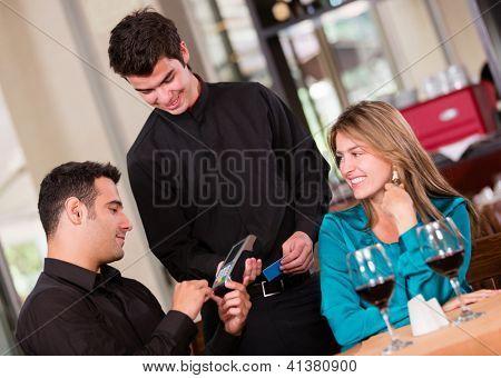 Mann, die Zahlung per Kreditkarte in einem restaurant