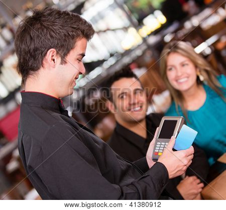 Couple paying by credit card at the restaurant