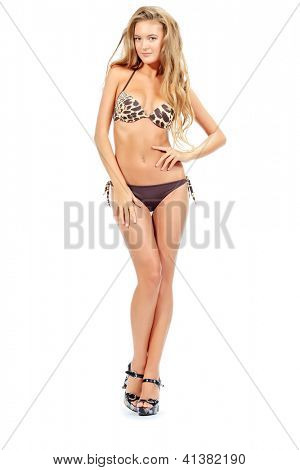 Full length portrait of a smiling young woman posing in bikini. Isolated over white background.