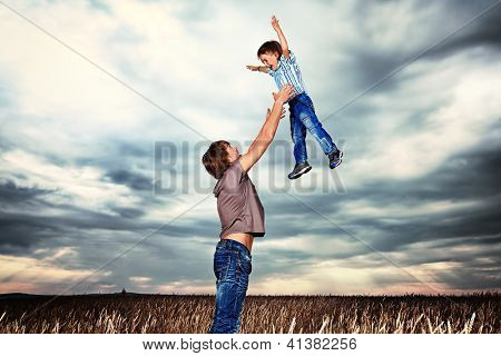 Happy father playing with his little son in the wheat field over beautiful cloudy sky.