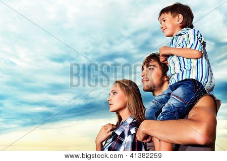 Happy family standing together over beautiful cloudy sky.