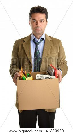 Fired businessman in a suit carrying a box of personal items isolated on white background