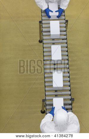 Visão aérea de dois trabalhadores em uniformes brancos trabalhando com caixas em linha de embalagem