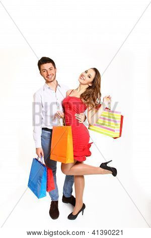 Happy Young Couple With Shopping Bags Isolated On White Bacgkround