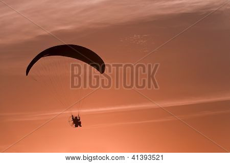 Paraglider silhouette at sunset