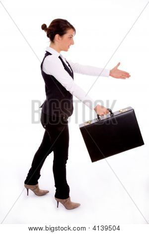 Businesswoman Holding Bag And Offering Handshake