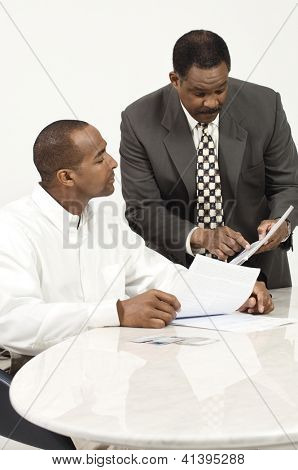 An African American business people discussing over financial bills in the office