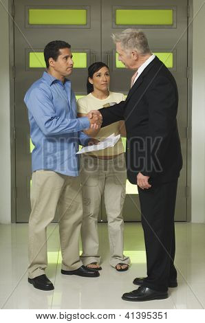 Full length of woman with man holding documents while shaking hand with senior businessman